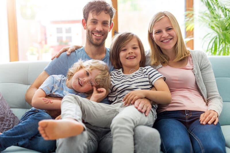 Fam?lia de sorriso no sof? imagens de stock royalty free