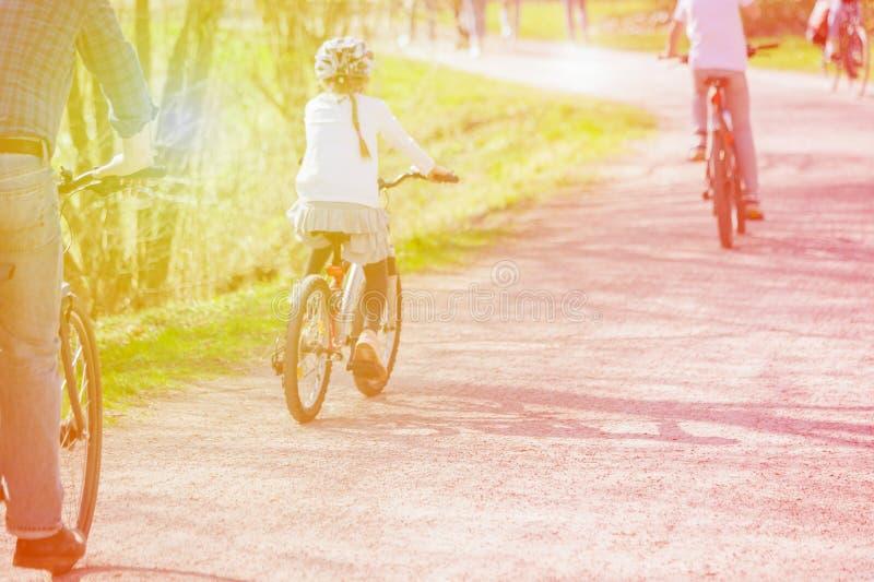 Fam?lia em bicicletas Conceito saud?vel do estilo de vida Ciclista da menina no capacete na estrada fora Dia ensolarado imagem de stock