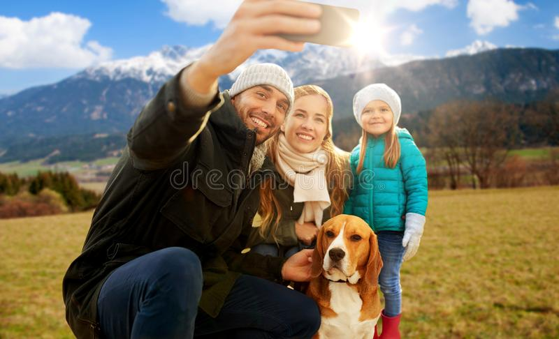 Fam?lia feliz com o c?o que toma o selfie no outono imagem de stock