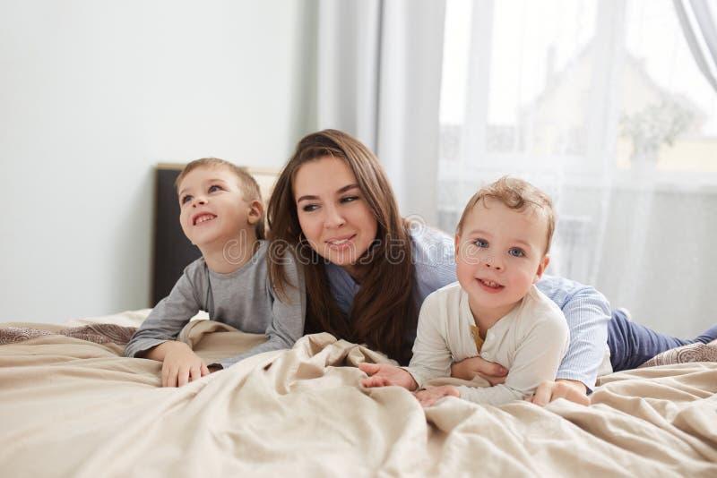 Fam?lia feliz M?e nova vestida em claro - o pijama azul coloca com seus dois filhos pequenos na cama com cobertura bege dentro foto de stock royalty free