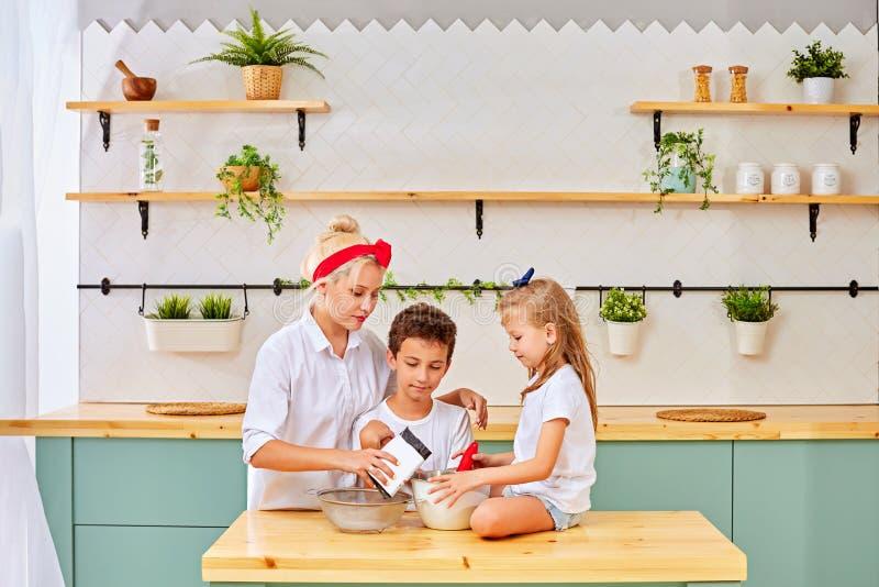 Fam?lia feliz na cozinha a m?e e as crian?as que preparam a massa, cozem cookies imagens de stock royalty free