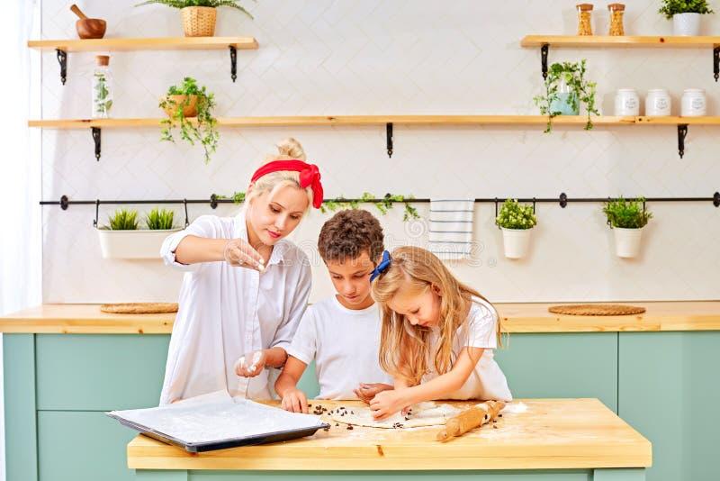Fam?lia feliz na cozinha a m?e e as crian?as que preparam a massa, cozem cookies fotografia de stock royalty free