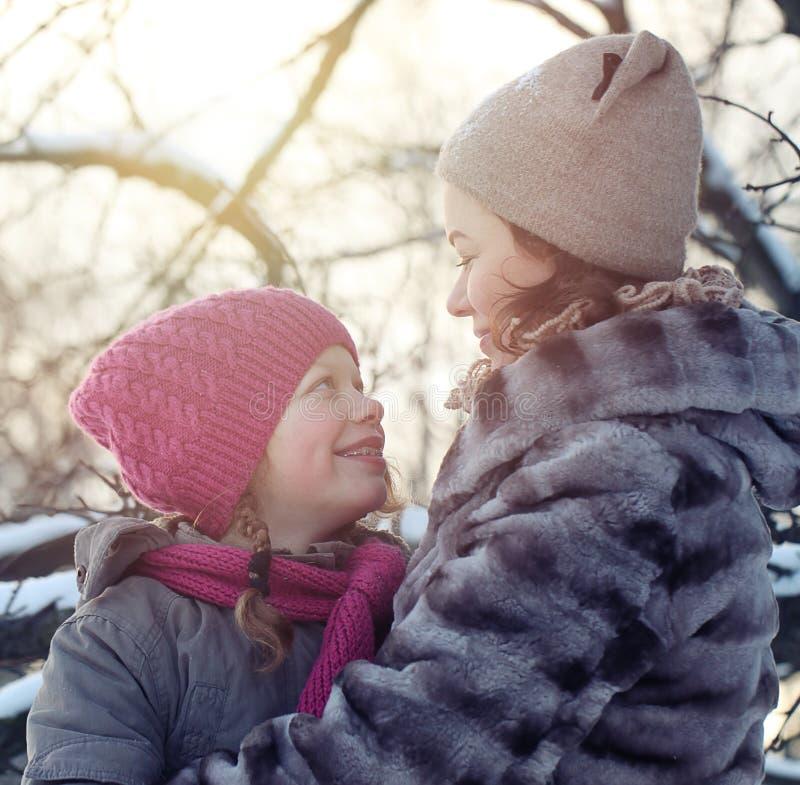 Fam?lia feliz no parque do inverno Matriz e filha que olham se fotografia de stock