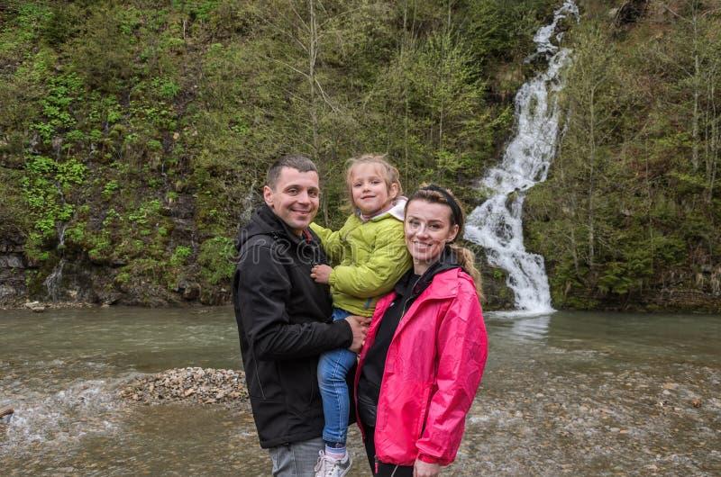 Fam?lia feliz nova: mam?, paizinho e filha no fundo de uma cachoeira da montanha fotos de stock royalty free