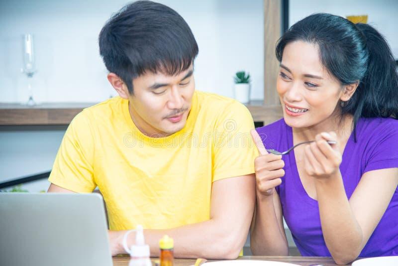 Fam?lia feliz Os pares bonitos asiáticos, a mulher bonita e o homem considerável estão tendo o café da manhã na cozinha foto de stock