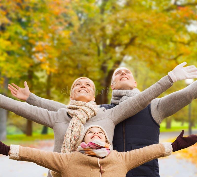 Fam?lia feliz que tem o divertimento no parque do outono imagens de stock