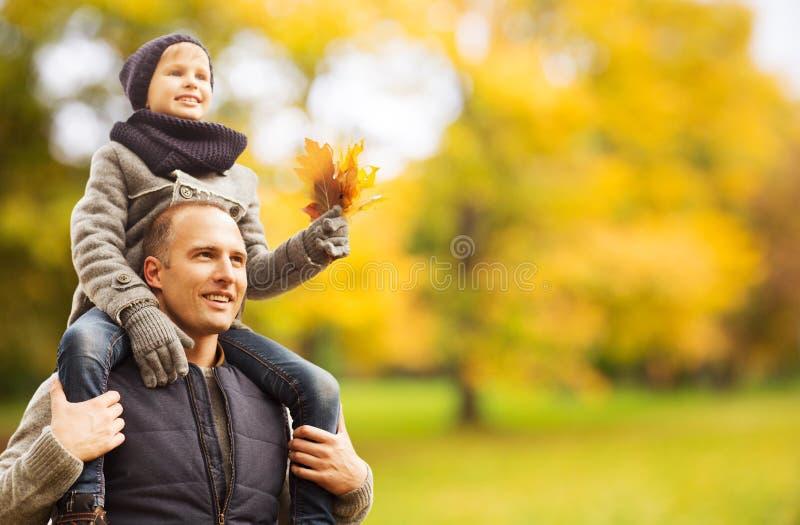Fam?lia feliz que tem o divertimento no parque do outono fotos de stock royalty free