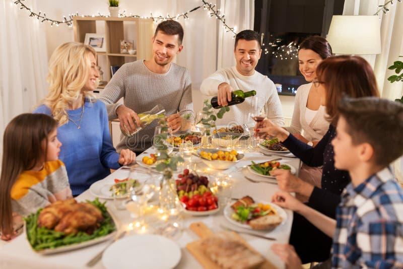 Fam?lia feliz que tem o partido de jantar em casa fotos de stock royalty free