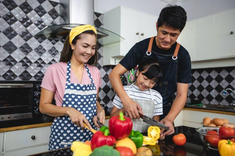 A fam?lia feliz tem o paizinho, a mam? e sua filha pequena cozinhando junto na cozinha fotografia de stock