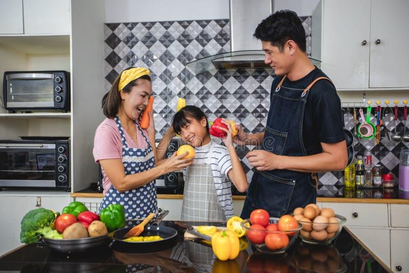 A fam?lia feliz tem o paizinho, a mam? e sua filha pequena cozinhando junto na cozinha fotografia de stock royalty free