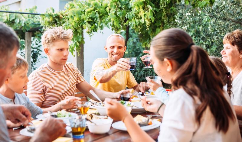 A fam?lia grande tem um jantar no ar livre no jardim do ver?o foto de stock royalty free
