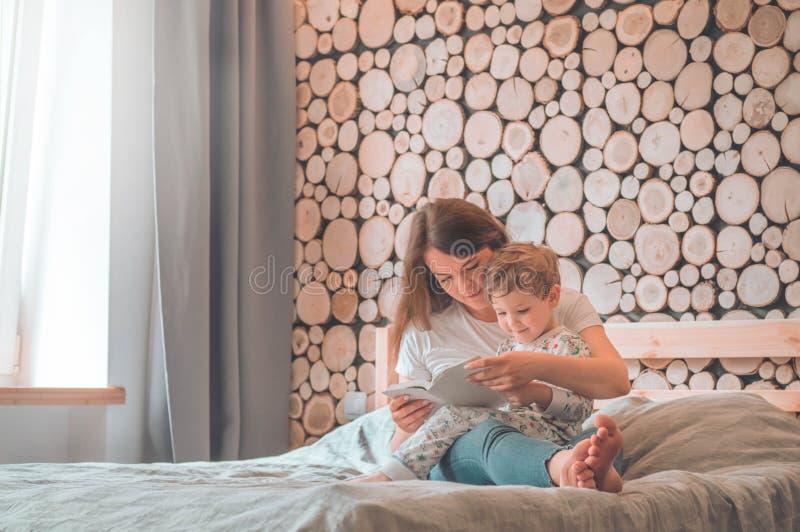 Fam?lia loving feliz Mãe nova bonita que lê um livro a seu filho pequeno fotos de stock royalty free