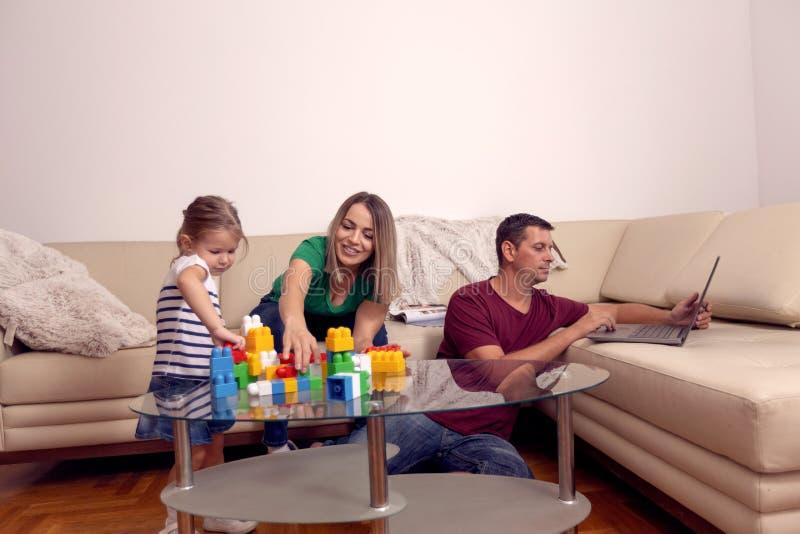 Fam?lia loving feliz pais que jogam com sua filha em casa foto de stock royalty free