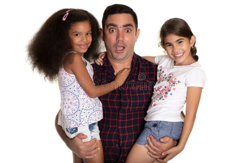 Fam?lia multirracial, pai latino-americano com uma express?o engra?ada que abra?a suas filhas da ra?a misturada fotos de stock royalty free
