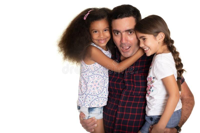 Fam?lia multirracial, pai latino-americano com uma express?o engra?ada que abra?a suas filhas da ra?a misturada foto de stock royalty free
