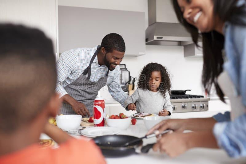 Fam?lia na cozinha em casa que faz panquecas junto foto de stock royalty free
