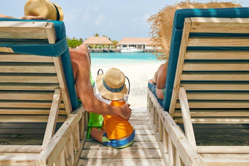 Fam?lia na praia em vadios de madeira da cama do sol foto de stock