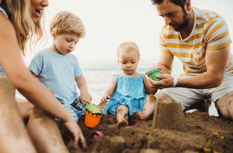 Fam?lia nova com as crian?as da crian?a que jogam com a areia na praia em f?rias de ver?o imagens de stock royalty free