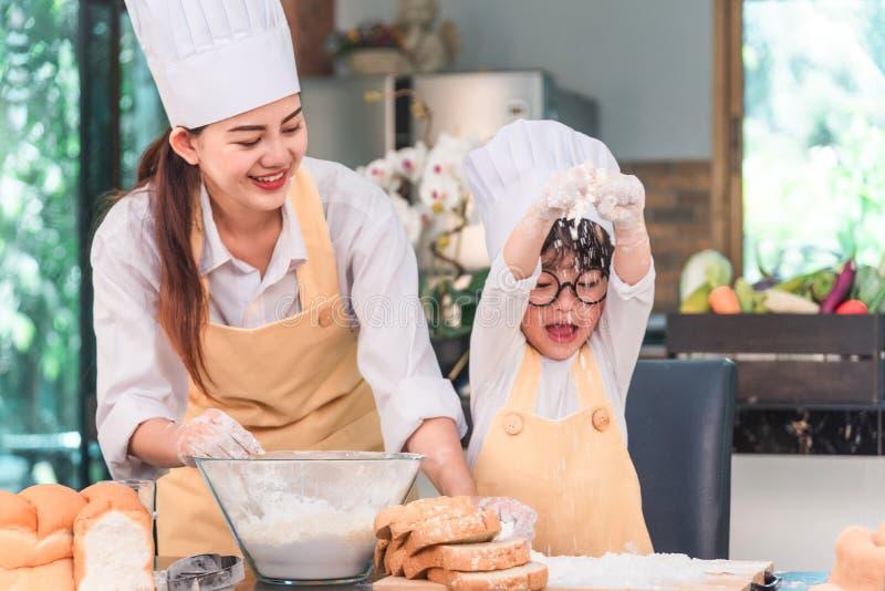 Fam?lia nova que cozinha o alimento na cozinha Mo?a feliz com sua massa de mistura da m?e na bacia imagens de stock