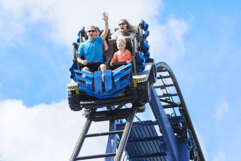 Fam?lia nova que tem o divertimento que monta um roller coaster em um parque tem?tico imagens de stock