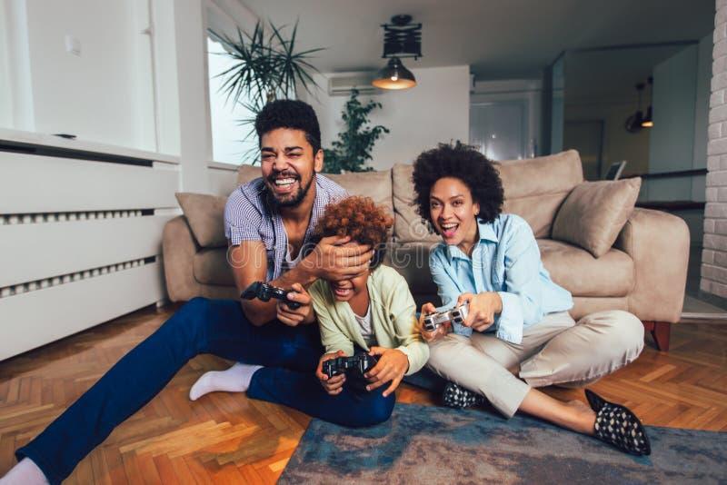 Fam?lia que senta-se no sof? que joga junto jogos de v?deo, foco seletivo imagem de stock royalty free