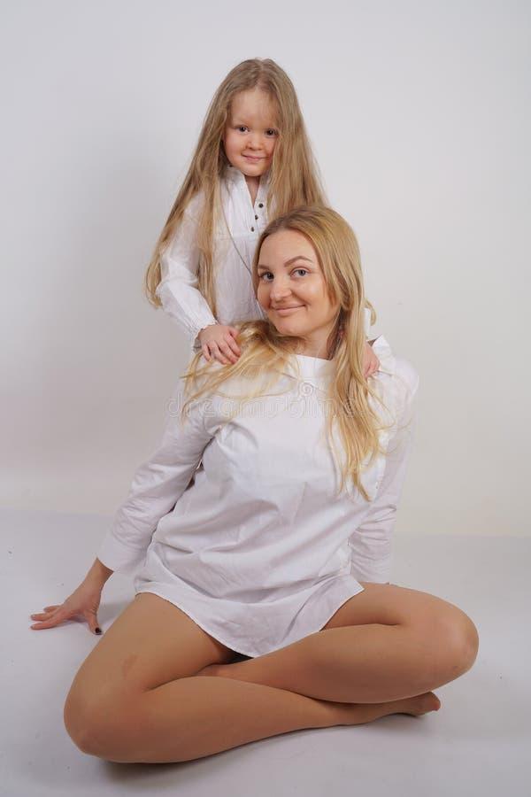 Fam?lia real da m?e e da filha caucasianos nas camisas brancas no fundo do est?dio foto de stock royalty free