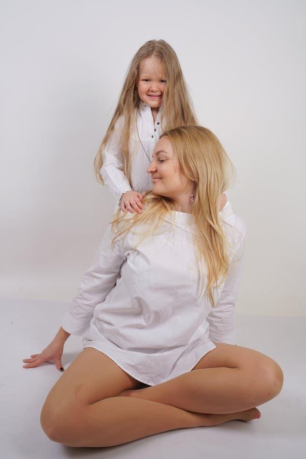 Fam?lia real da m?e e da filha caucasianos nas camisas brancas no fundo do est?dio fotografia de stock royalty free