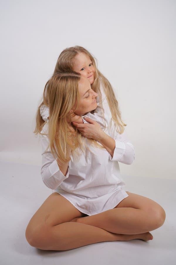 Fam?lia real da m?e e da filha caucasianos nas camisas brancas no fundo do est?dio imagem de stock