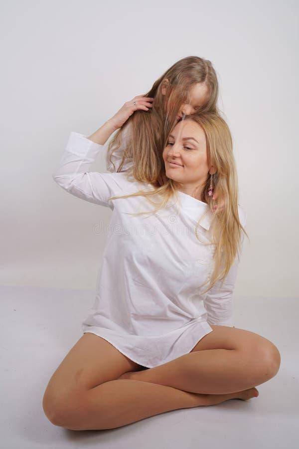 Fam?lia real da m?e e da filha caucasianos nas camisas brancas no fundo do est?dio foto de stock