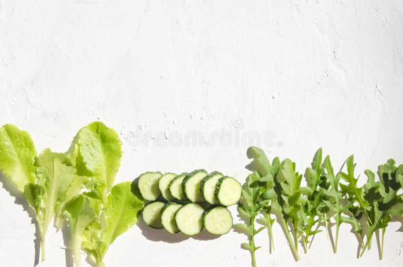 Fama hecha de partes verdes de la lechuga, del arugula y del frsh del cucumnber en la superficie blanca Espacio vac?o para el dis fotografía de archivo