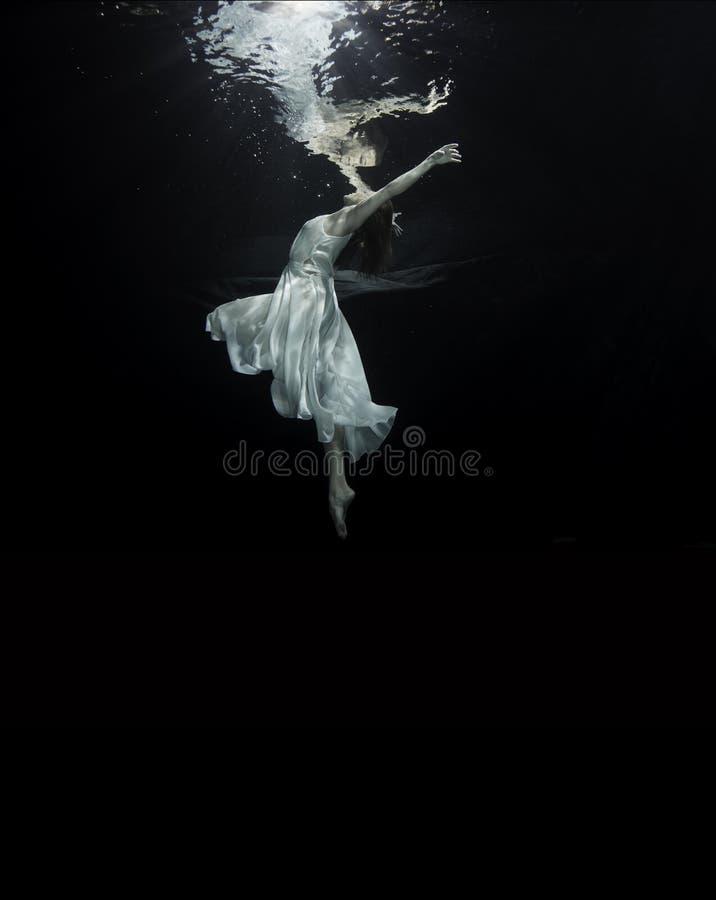 Ballerina underwater. A young famale ballet dancers is dancing underwater royalty free stock image