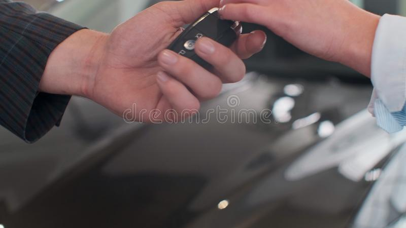Famale hand gives a car keys to male hand in the car dealership close up. Unrecognized auto seller and a woman who stock photos