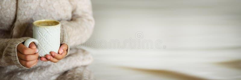 Famalehanden die een comfortabele ceramische met de hand gemaakte mok met coffe houden De winter en Kerstmis het concept van de h royalty-vrije stock fotografie