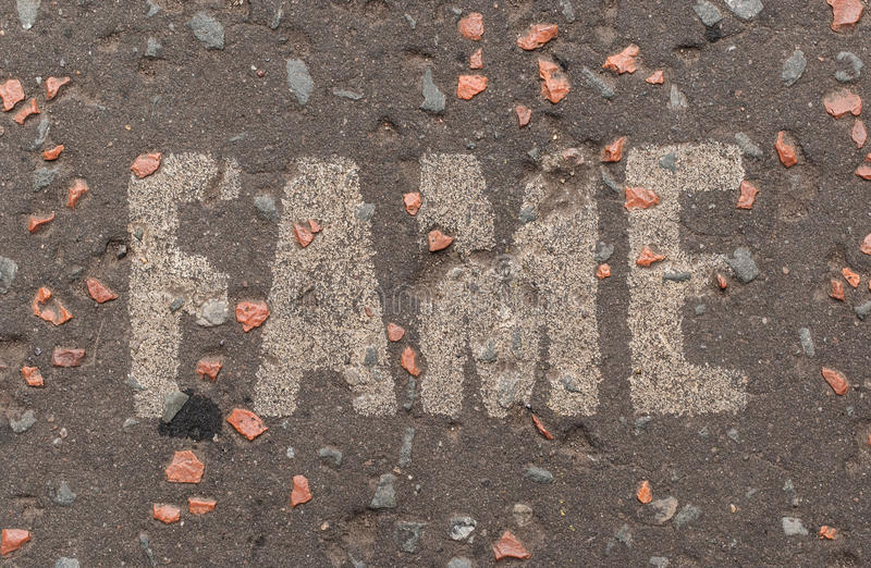 Fame written in white capital letters on a street pavement. In Edinburgh, UK royalty free stock image