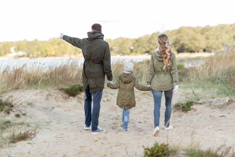Happy family walking along autumn beach stock photo
