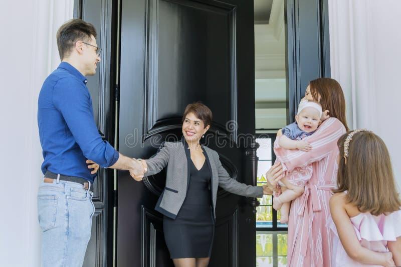 Famiglia accolta dal loro agente immobiliare per entrare in casa fotografia stock libera da diritti