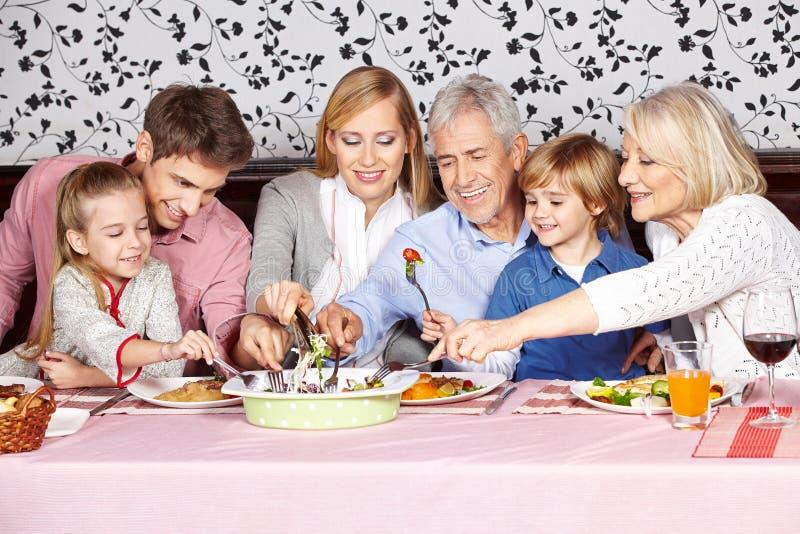 Famiglia affamata che raggiunge per l'alimento a fotografie stock