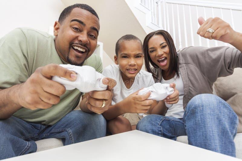 Famiglia afroamericana divertendosi giocando il videogioco del computer immagini stock libere da diritti