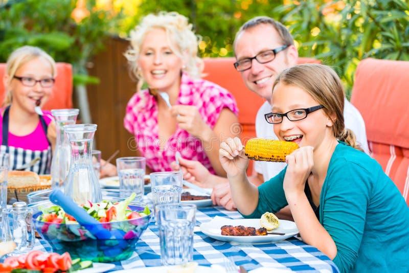 Famiglia al cibo nel barbecue del giardino immagine stock libera da diritti