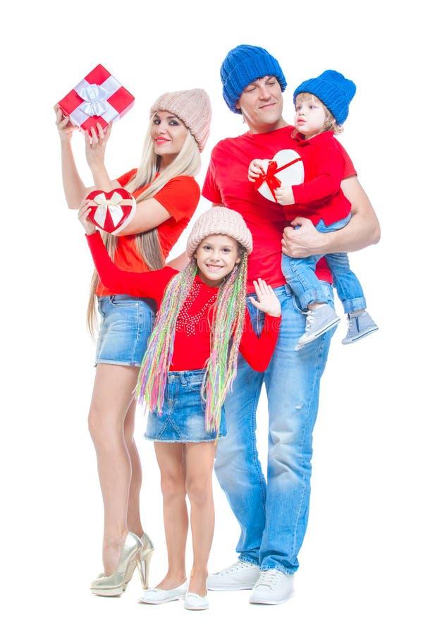 Famiglia al Natale Famiglia allegra in cappelli che esaminano macchina fotografica e che sorridono mentre isolato su bianco Conte immagine stock