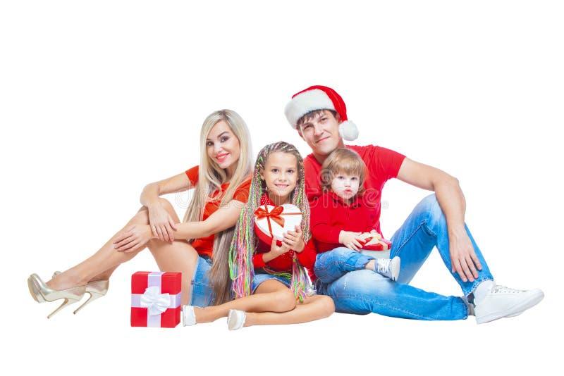Famiglia al Natale Famiglia allegra in cappelli di Santa che esaminano macchina fotografica e che sorridono mentre isolato su bia immagine stock libera da diritti