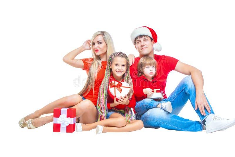 Famiglia al Natale Famiglia allegra in cappelli di Santa che esaminano macchina fotografica e che sorridono mentre isolato su bia immagini stock