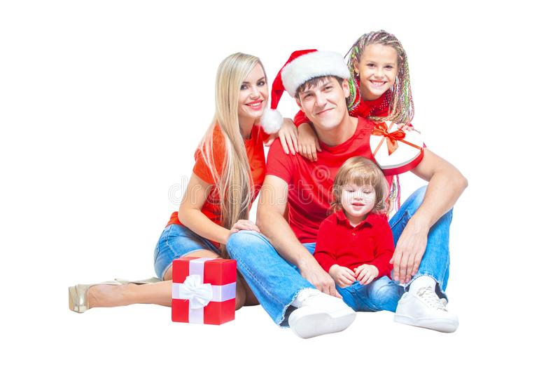 Famiglia al Natale Famiglia allegra in cappelli di Santa che esaminano macchina fotografica e che sorridono mentre isolato su bia fotografie stock