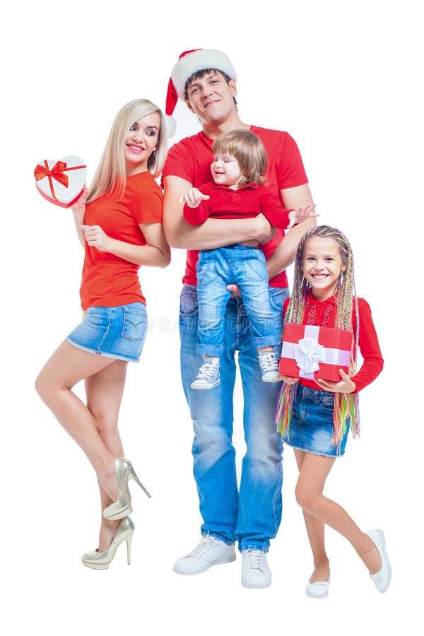 Famiglia al Natale Famiglia allegra in cappelli di Santa che esaminano macchina fotografica e che sorridono mentre isolato su bia fotografia stock