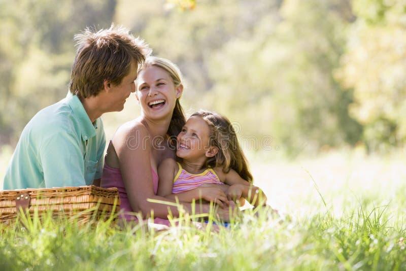 Famiglia alla sosta che ha un picnic e una risata fotografia stock libera da diritti