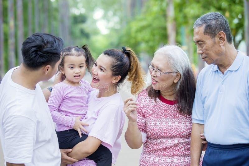 Famiglia allargata che chiacchiera all'aria aperta immagine stock libera da diritti