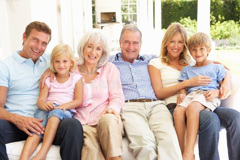 Famiglia allargata che si distende insieme sul sofà fotografia stock libera da diritti