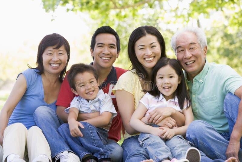 Famiglia allargata che si siede all'aperto sorridere immagini stock