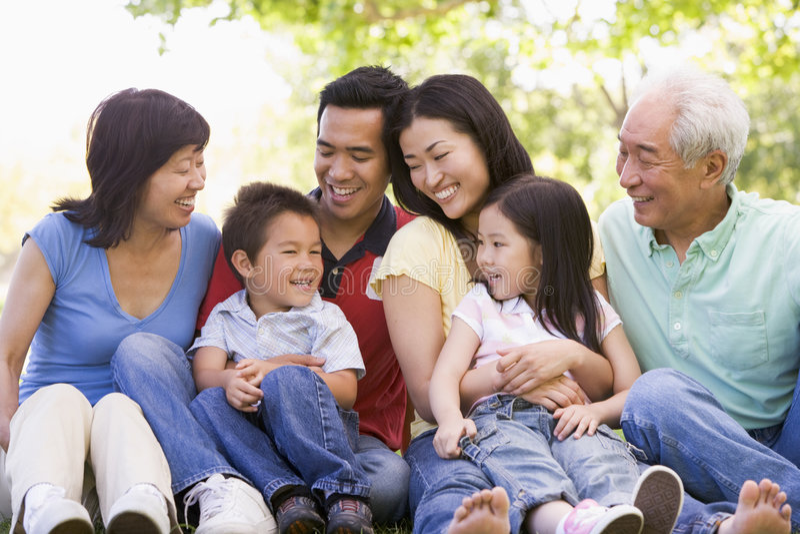 Famiglia allargata che si siede all'aperto sorridere immagine stock