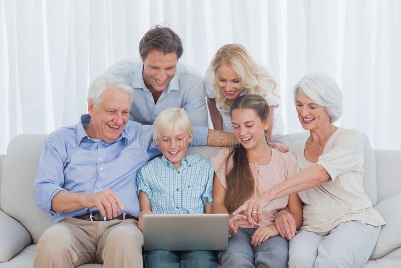 Famiglia allargata che si siede sul sofà fotografia stock libera da diritti